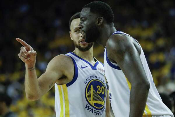 Golden State Warriors Stephen Curry and Draymond Green talk in the fourth quarter during game 1 of the Western Conference Semifinals between the Golden State Warriors and the Houston Rockets at Oracle Arena on Sunday, April 28, 2019 in Oakland, Calif.