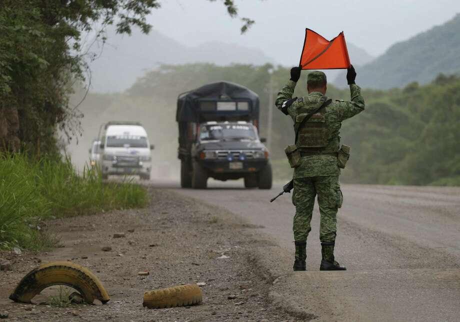 Un soldado de la Guardia Nacional de México hace señales a los vehículos para que se detengan en un punto de revisión temporal en Chiapas, México. Photo: Rebecca Blackwell /Associated Press / Copyright 2019 The Associated Press. All rights reserved.