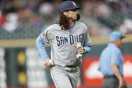 San Diego Padres pinch hitter Matt Strahm heads back to the dugout after drawing a walk with the bases loaded to force in the go-ahead run off Colorado Rockies relief pitcher Jon Gray in the ninth inning of a baseball game Sunday, June 16, 2019, in Denver. (AP Photo/David Zalubowski)