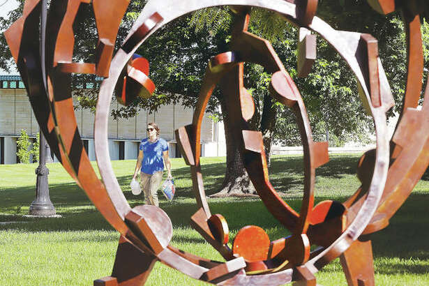 """A woman walks across the Lewis and Clark Community College campus Thursday as seen through the 2010 bronze sculpture by artist Joel Perlman called """"Rolling on the River"""". The college's Board of Trustees moved forward with a proposed 2020 budget last week, despite a level of apparently disagreement on some line items, including money to purchase art for display on campus. Final vote will be July 9."""
