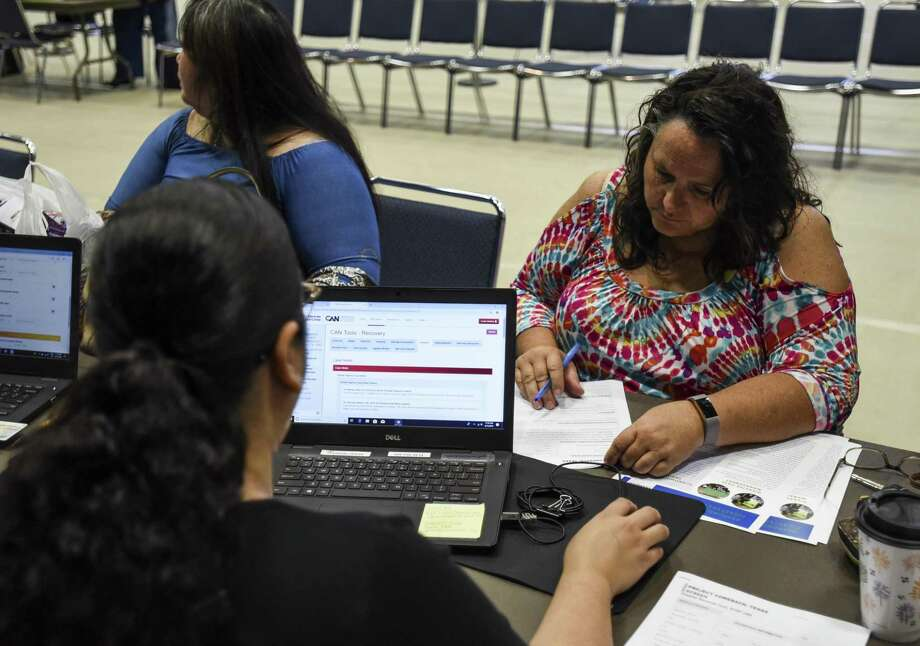 Kim Therrien talks to a worker with the Disaster Services Corporation during a public forum and resource fair for disaster recovery in Port Arthur in the Carl A. Parker Multipurpose Center Saturday. Photo taken on Saturday, 06/15/19. Ryan Welch/The Enterprise Photo: Ryan Welch, Beuamont Enterprise / The Enterprise / © 2019 Beaumont Enterprise