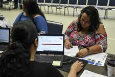 Kim Therrien talks to a worker with the Disaster Services Corporation during a public forum and resource fair for disaster recovery in Port Arthur in the Carl A. Parker Multipurpose Center Saturday. Photo taken on Saturday, 06/15/19. Ryan Welch/The Enterprise