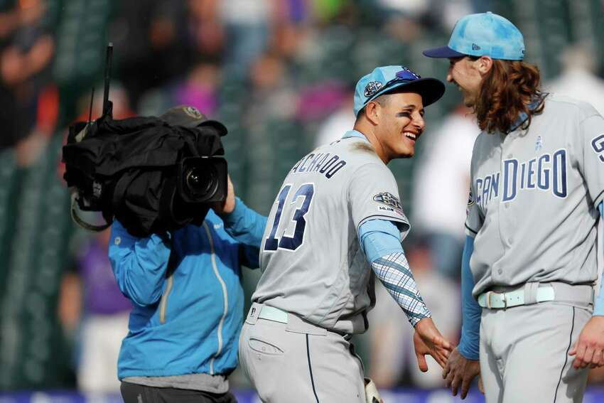 San Diego Padres third baseman Manny Machado (13) congratulates pitcher Matt Strahm after a baseball game against the Colorado Rockies, Sunday, June 16, 2019, in Denver. Strahm drew a bases-loaded walk as a pinch hitter to force in the go-ahead run in the Padres' victory. (AP Photo/David Zalubowski)