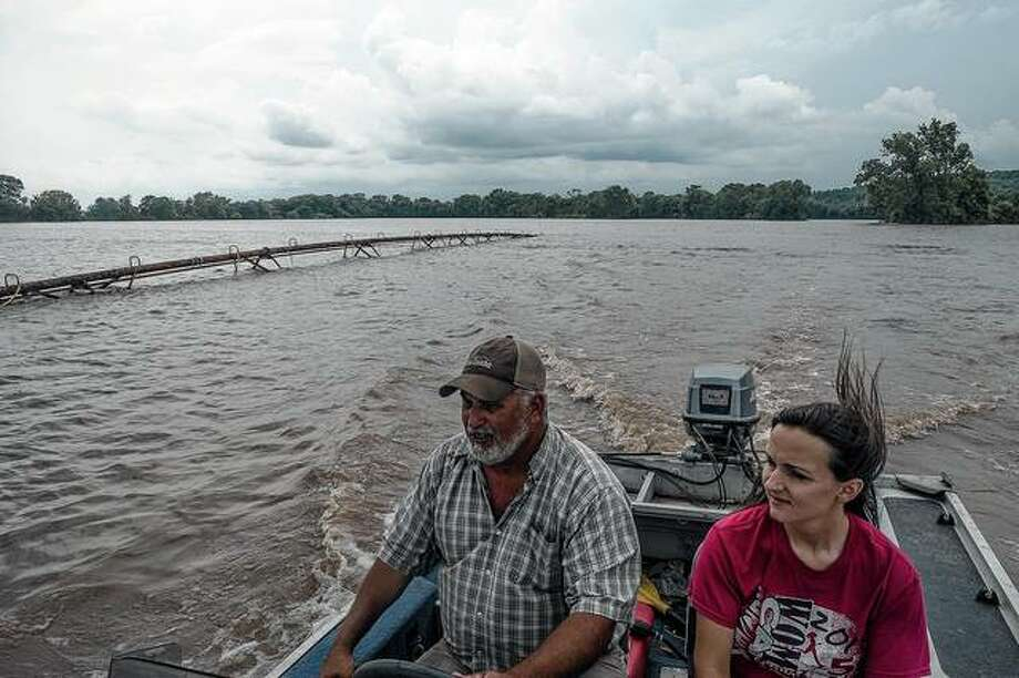 Chris Schaefers (left) and his neighbor and fellow farmer, Jill Edwards, pass an irrigation system nearly covered by floodwaters in swamped crop fields. Fast currents and swollen channels have rendered many rivers unsafe for commercial traffic, spreading economic pain from a spring of severe floods. Photo: Joseph Rushmore | The New York Times