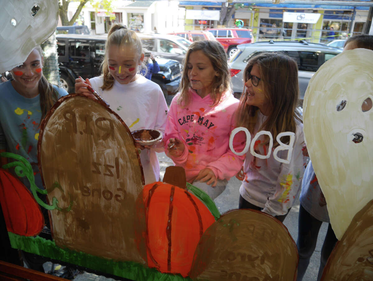 East Ridge Middle School students paint the window in front of Planet Pizza during Fall in Love With Ridgefield in 2016.