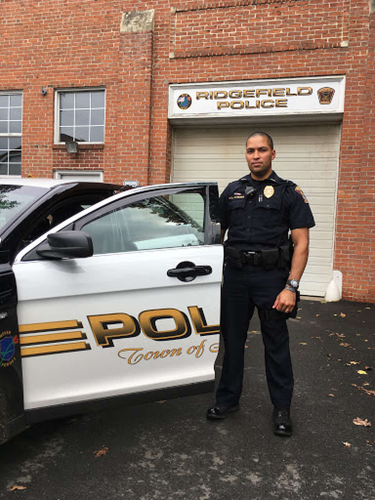 Ridgefield police officer Carlos Olivares stands in front of his cruiser behind police headquarters. He joined the force on Sept. 21. - Peter Yankowski photo