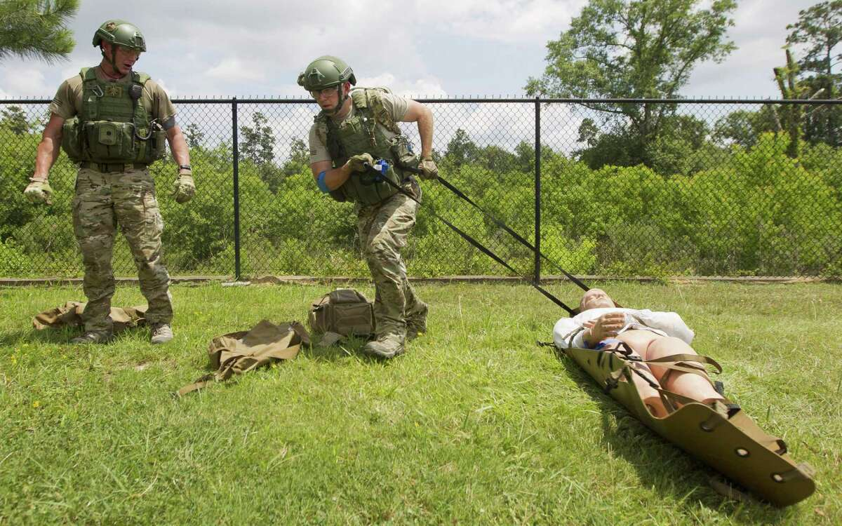 Medic Mike Joublanc, left, works to transport manikin alongside partner Peter Ledet after applying a tourniquet as members of the Montgomery County Hospital District's EMS SWAT team takes part in emergency scenarios as part of the group's monthly training, Monday, June 10, 2019, in Conroe.