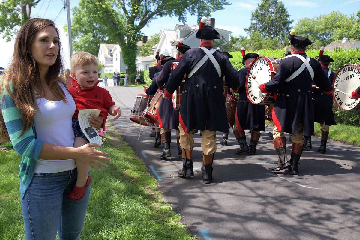 Chelsey Palmer of Fairfield her son Matthew, 2, watch the parade heads to the Lower Harbor at the Blessing of the Fleet and the Southport Street Parade on Saturday, June 15, 2019, in Fairfield, Conn.