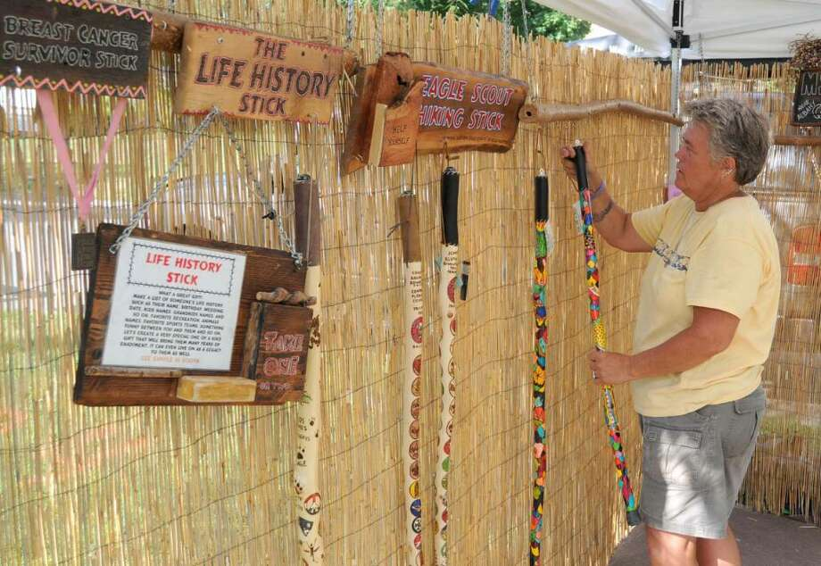 Debi Hitter, of Castleton, N.Y., sets up her display of custom designed Life History Sticks, at the Greater New Milford Chamber of Commerce Village Fair Days, on Thursday, July 29, 2010. Each of Hitter's walking sticks is designed with graphics and lettering  to tell a story. She is licensed by the Boy Scouts of America to do their eagle scout walking sticks. Photo: Jay Weir / The News-Times Freelance
