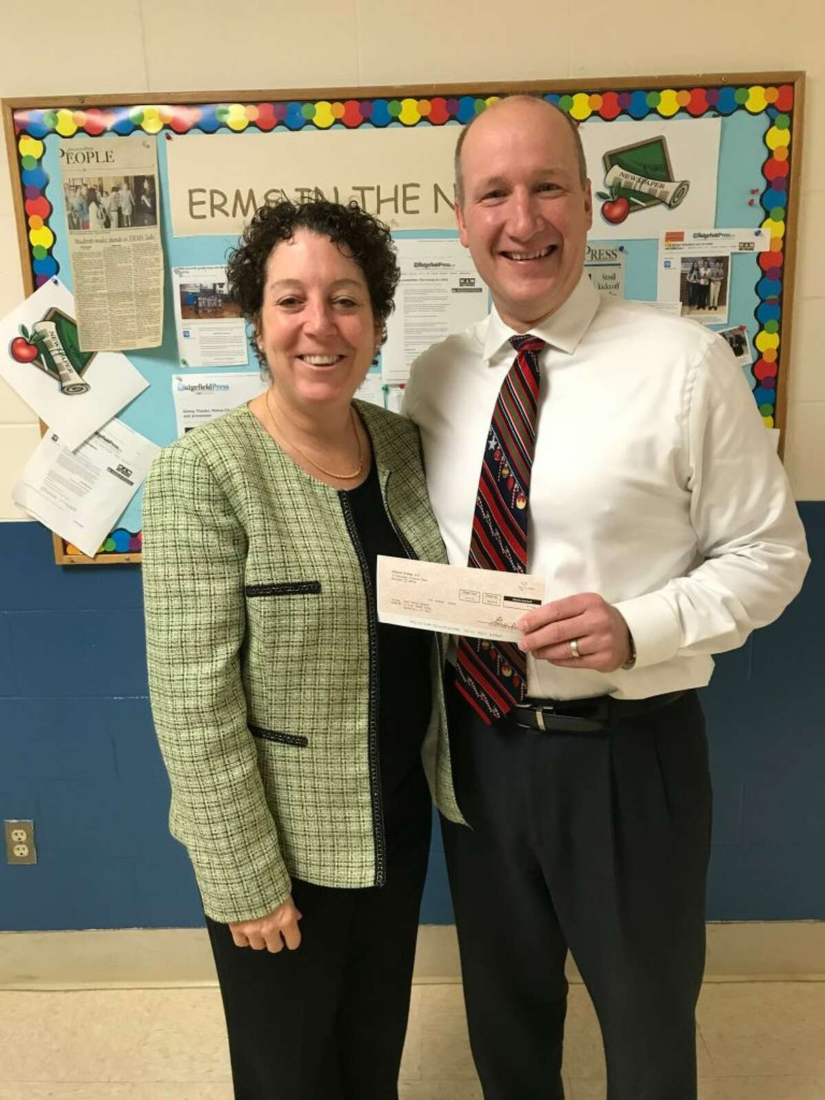 Mobil co-owner Todd Schoenherr with East Ridge Middle School principal Patricia Raneri in December.