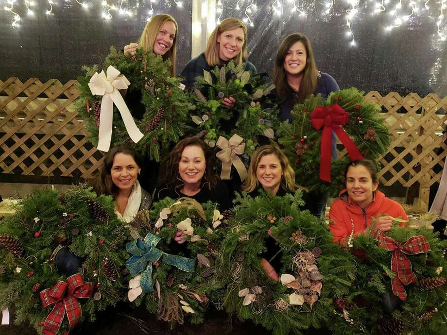 Local women show off their decorated wreaths at Woodcock Nature Center.
