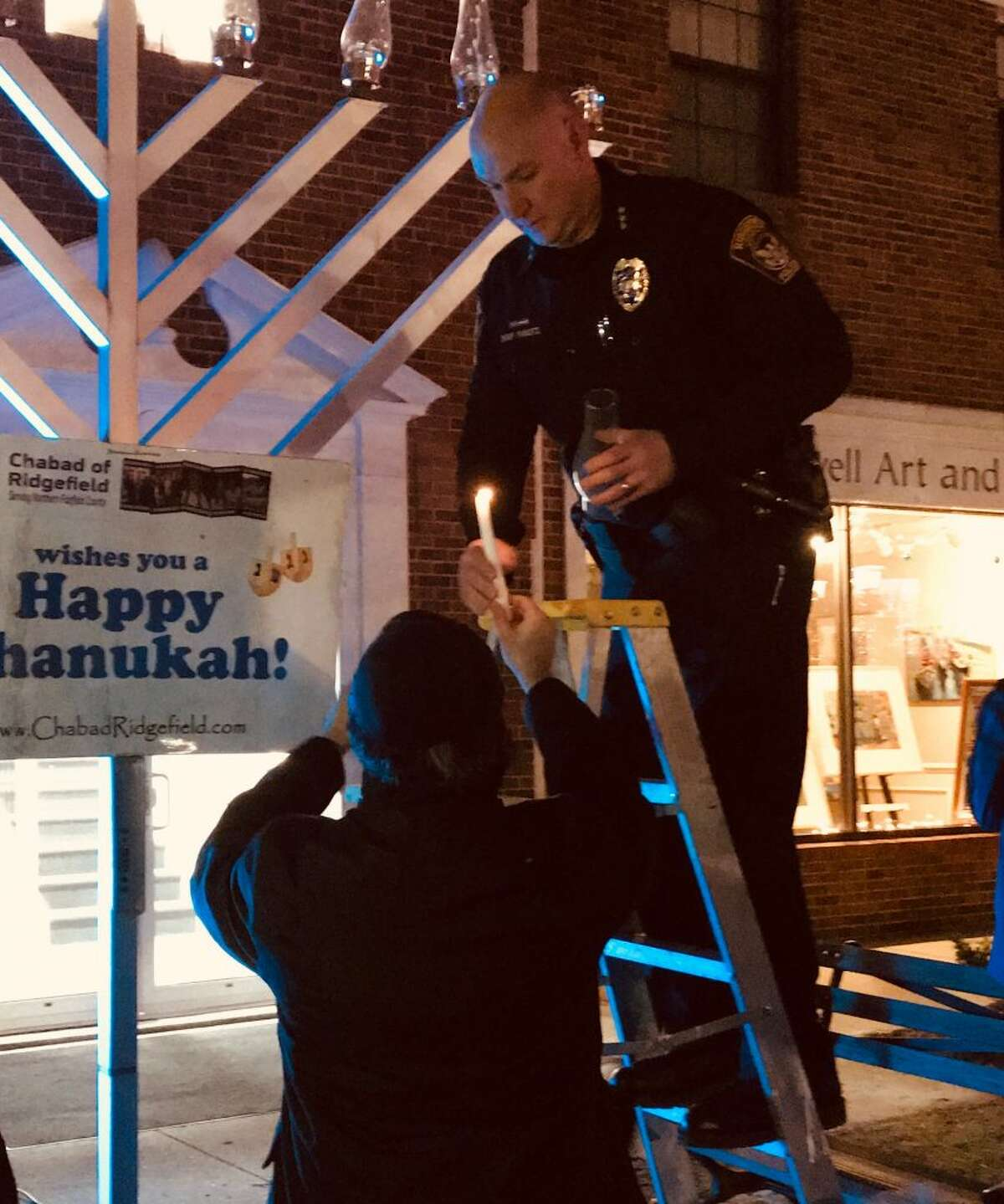 Police Chief Jeff Kreitz lights a candle during the Hanukah walk on Main Street on Dec. 7.