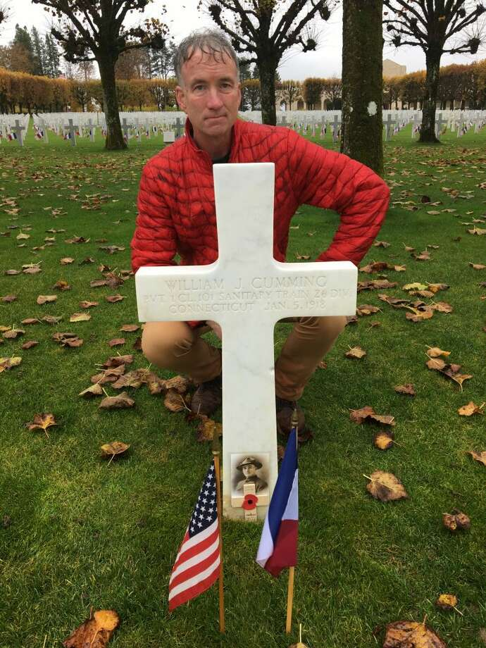 Ridgefield resident Keith Miller poses with the memorial cross of Ridgefield native William Cumming who died of pneumonia in World War I and is buried with 14,000 other Americans in the Meuse Argonne Cemetery in France.
