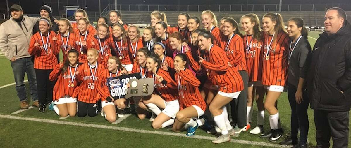 The Ridgefield High girls soccer team celebrates its 1-0 win over Staples in the Class LL state finals. - Tim Murphy photo