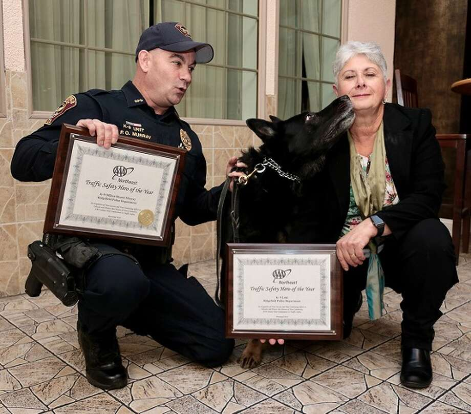 "Ridgefield Police Department K9 officer Loki, a German Shepherd, gives AAA Northeast's Fran Mayko, right, a thank you kiss for his AAA Traffic Safety Hero award as his very surprised partner, K9 Officer Shawn Murray, another ""Hero"" looks on."
