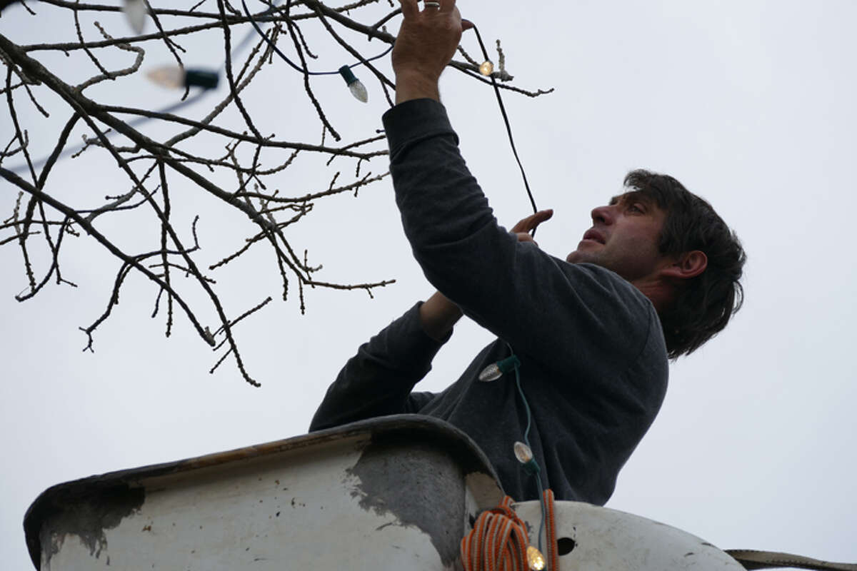 Eric Hochadel hangs the holiday lights on Main Street Thursday, Nov. 1. The holiday season is officially arrived in Ridgefield. The annual flipping of the switch will happen Friday, Nov. 23. - Peter Yankowski photo