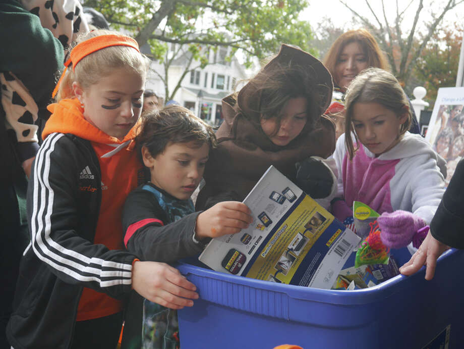 Young trick-or-treaters reach inside the giveaway bin outside the Toy Chest during last fall's Halloween Walk. — Steve Coulter photo