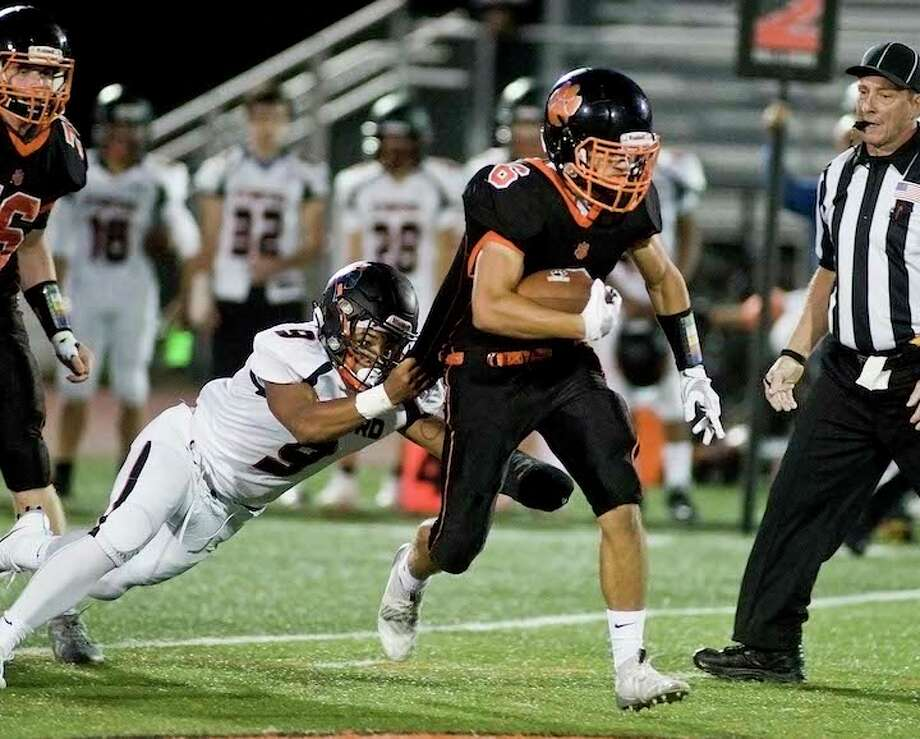 Jack Englert takes a Stamford defender along for the ride during a run Friday night. — Scott Mullin photo / Scott Mullin ownership