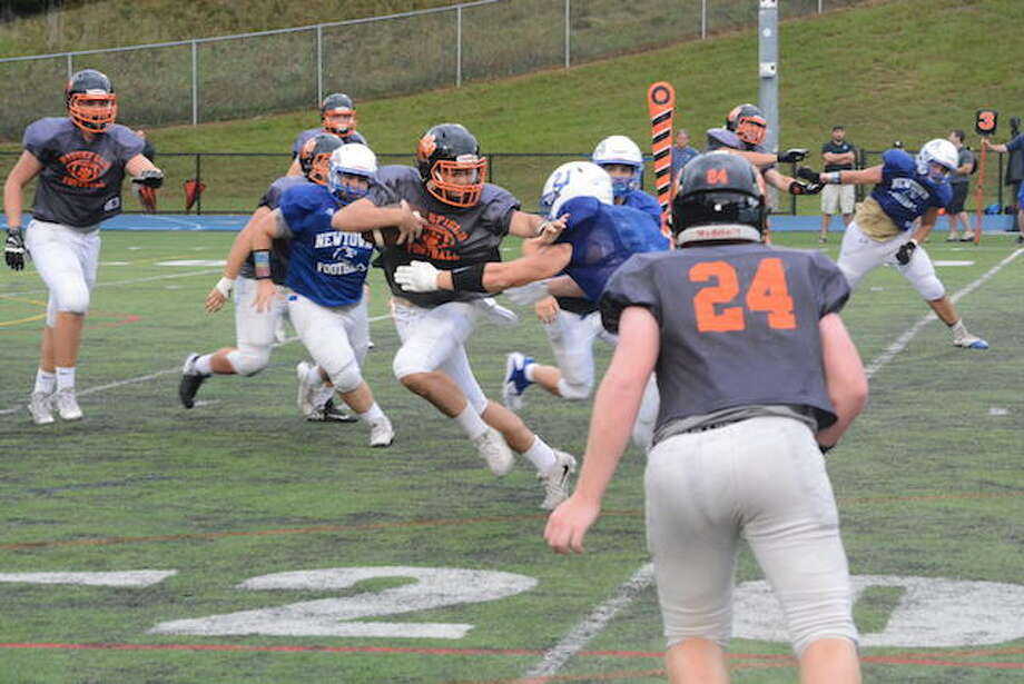 Junior quarterback Owen Matthews runs with the ball during a scrimmage in Newtown last week. — Andy Hutchison photo