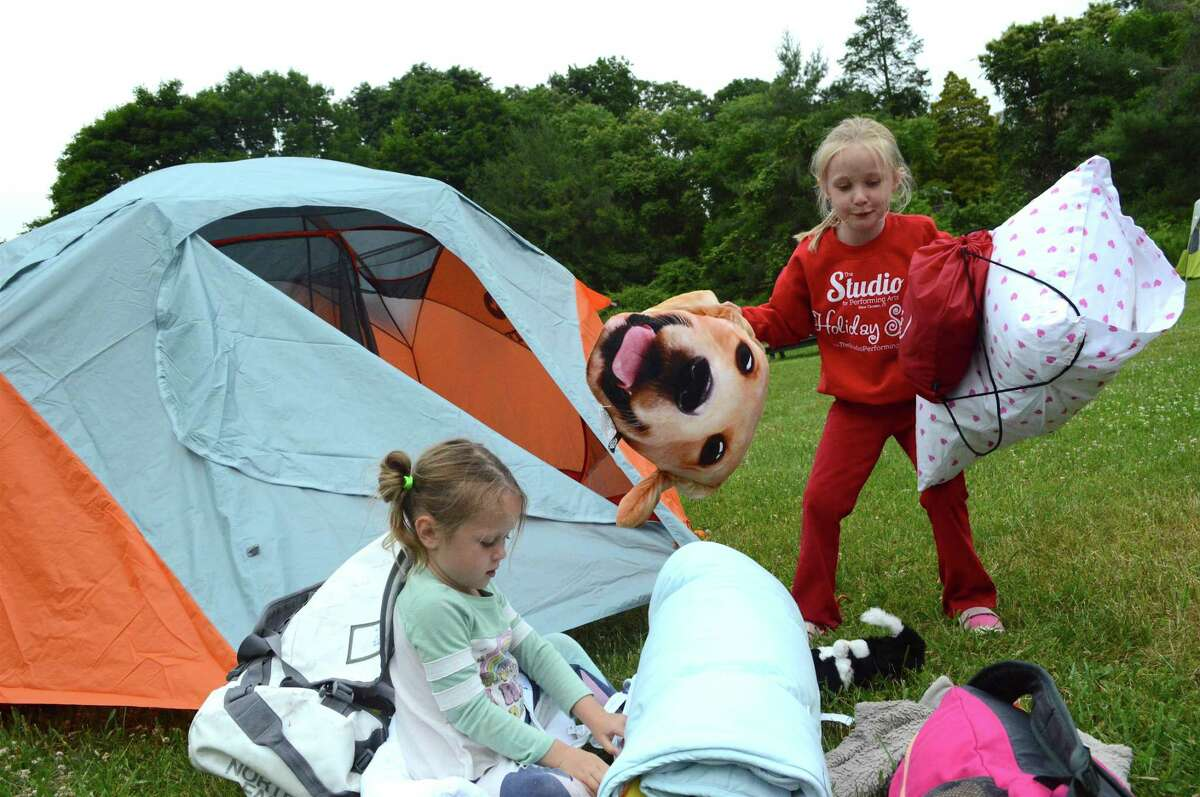 Marin Fleischmann, 6, right, of New Canaan, and her sister, Paloma, 4, load some of the essentials into the tent at the Great American Campout at the New Canaan Nature Center last year in New Canaan. The event returns June 22-June 23.