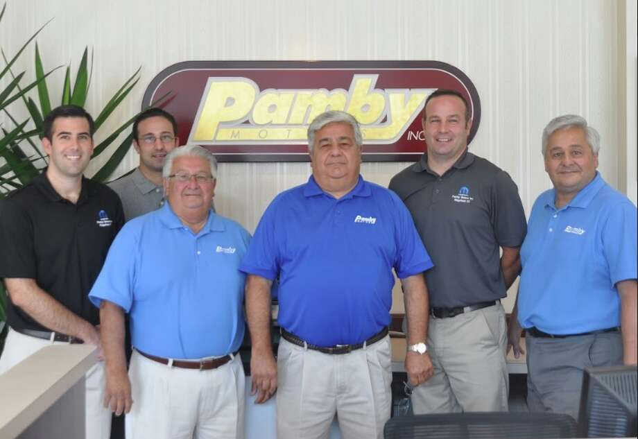 At the front desk of Pamby Motors showroom are six Pambianchi men representing two generations: From left, Nick, Andy, John, Mike, Tim and Fred. —Macklin Reid photo