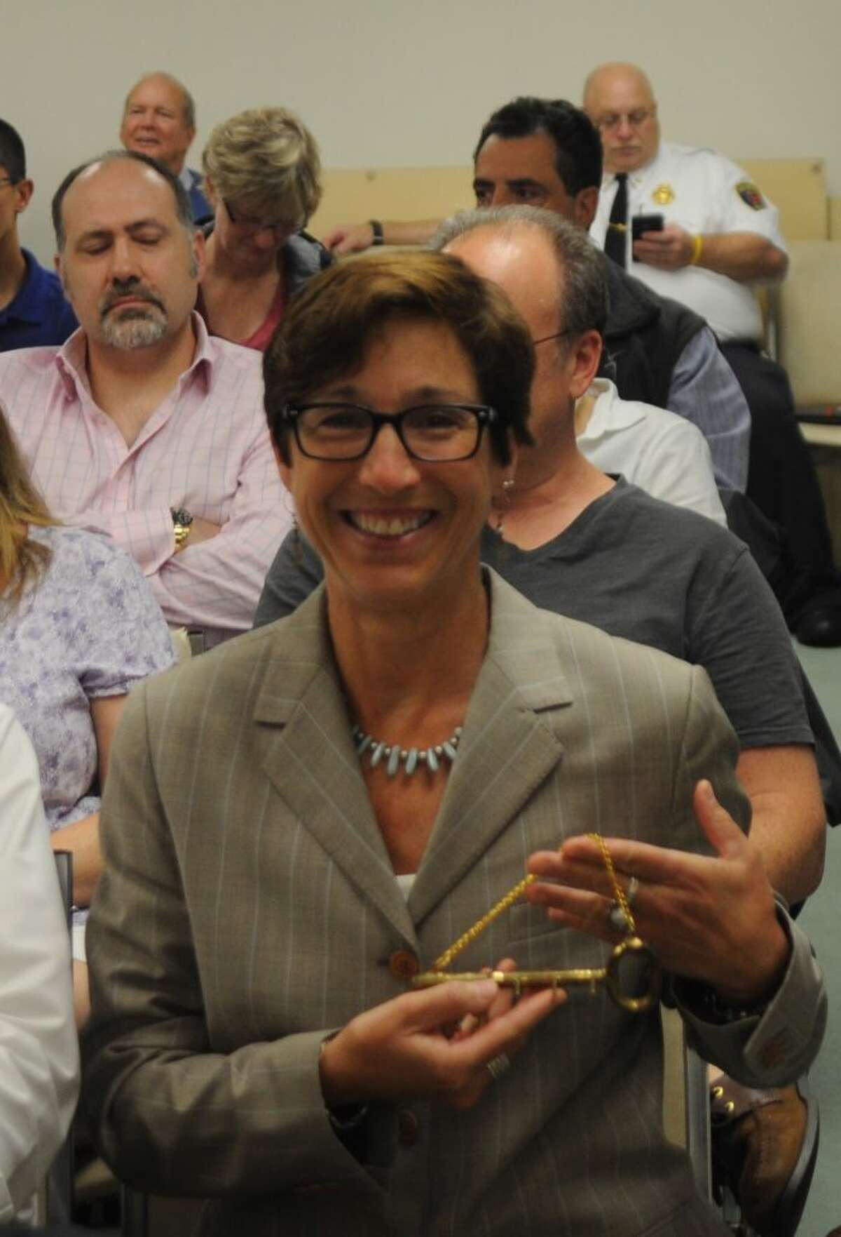 """Wendy Lionetti, new town clerk, displays the ceremonial """"key to the office"""" presented to her Monday night by retiring Town Clerk Barbara Serfilippi. - Macklin Reid photo"""