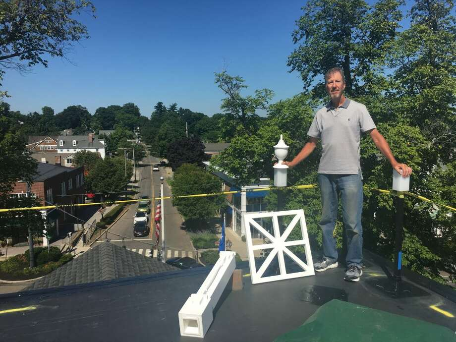 Carpenter Mike Wise stands atop town hall, where he's building a section of recreated decorative railing known as the widow's walk. — Steve Coulter photo