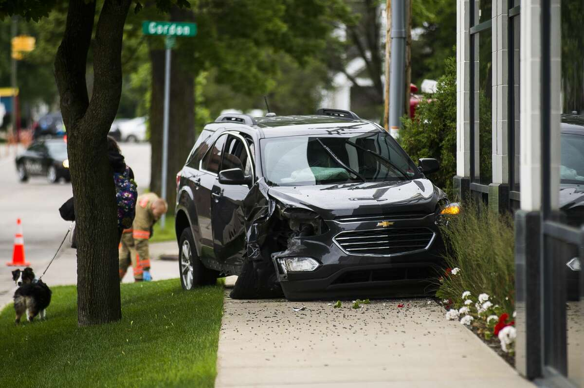 Midland police and firefighters secure the scene of a crash involving two vehicles, which left one vehicle totaled and the southwest window of a Midland realty business severely damaged, on Monday, June 17, 2019 near the intersection of Gordon and Buttles. (Katy Kildee/kkildee@mdn.net)