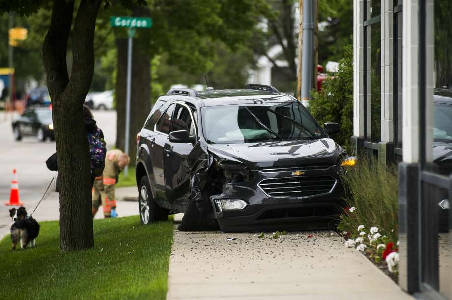 Midland police and firefighters secure the scene of a crash involving two vehicles, which left one vehicle totaled and the southwest window of a Midland realty business severely damaged, on Monday, June 17, 2019 near the intersection of Gordon and Buttles. (Katy Kildee/kkildee@mdn.net) Photo: (Katy Kildee/kkildee@mdn.net)