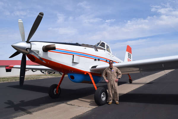 Michael Rutledge stands next to his ride, an 800-gallon firefighting airplane, during a visit to the Plainview-Hale County Airport.