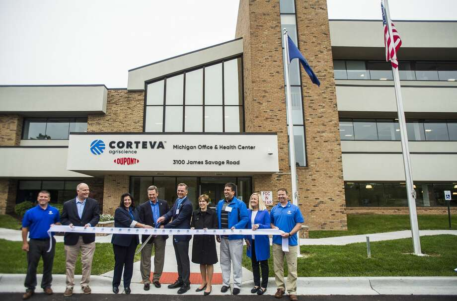 U.S. Rep. John Moolenaar, second from left, Susan Lewis, senior vice president of enterprise operations for Corteva Agriscience, third from left, Jim Collins, chief executive officer of Corteva Agriscience, fourth from left, David Midkiff, director of operations for Corteva Agriscience, fifth from left, and Midland Mayor Maureen Donker, fifth from left, along with additional Corteva staff, pose for a photo before cutting a ribbon during an event celebrating the agriculture company on Monday, June 17, 2019 at 3100 James Savage Road in Midland. (Katy Kildee/kkildee@mdn.net) Photo: (Katy Kildee/kkildee@mdn.net)