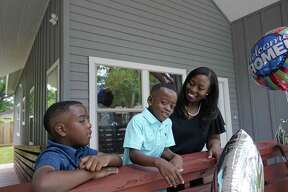Sabrina Starks-Tarble with her sons, Drew Tarble, 9, and Cameron Tarble, 5, stand on the front porch of their new home in Acres Home Friday, June 7, 2019, in Houston. She purchased the home through the Houston Community Land Trust.
