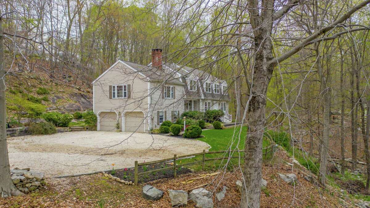 The very private woodland setting of this house has a sizable parking area, large rock outcroppings in the backyard, and professional landscaping.