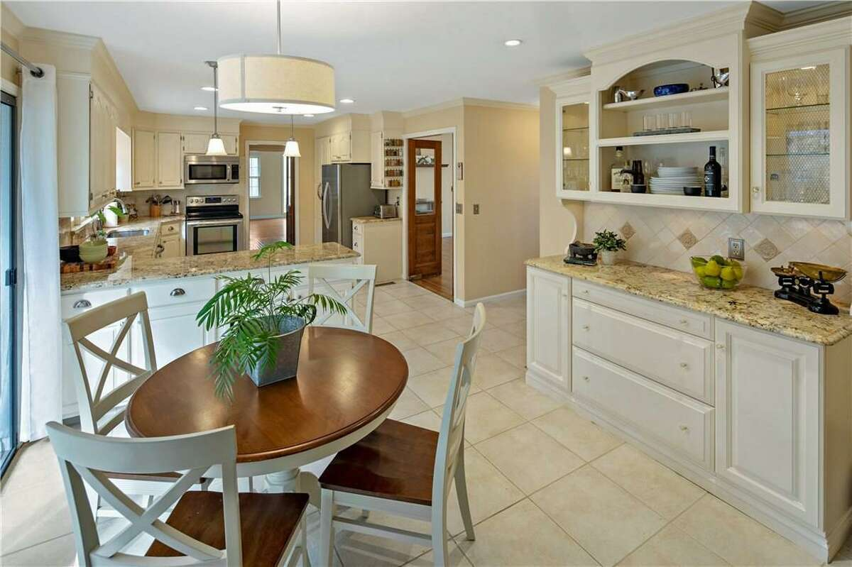 The eat-in area of kitchen has a built-in hutch and sliding doors to the deck.