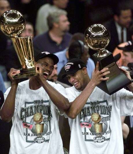 David Robinson, left, holds the NBA championship trophy as teammate Tim Duncan holds the Most Valuable Player trophy after defeating the New York Knicks 78-77 in Game 5 of the 1999 NBA Finals Friday, June 25, 1999, at New York's Madison Square Garden. Photo: MARK LENNIHAN /AP / AP