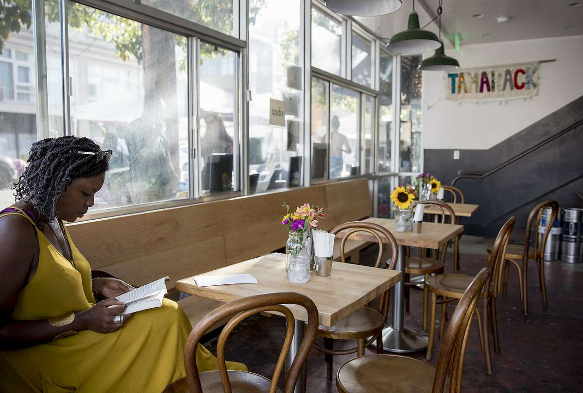 A woman reads a book while waiting for her food order at Tamarack in Oakland, Calif. Saturday, June 8, 2019.