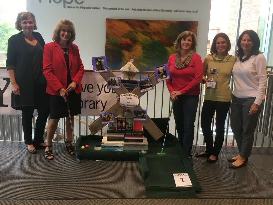 How does the Ridgefield Library become a 18-hole mini golf course? Just ask Love Your Library organizers Magda Fincham, Laureen Bubniak, Julie Yaun, Tizzie Mantione and Connie Marsala. The two-day event kicks off with Teen Night for young golfers from 6:30 to 10 Friday, Sept. 28. Family Open Play golf will be held 10 a.m. to 4 p.m. Saturday, Sept. 29, concluding with The Challenge Cup (which Mantione is holding in the above photo) at 7:30 p.m. — Steve Coulter photo