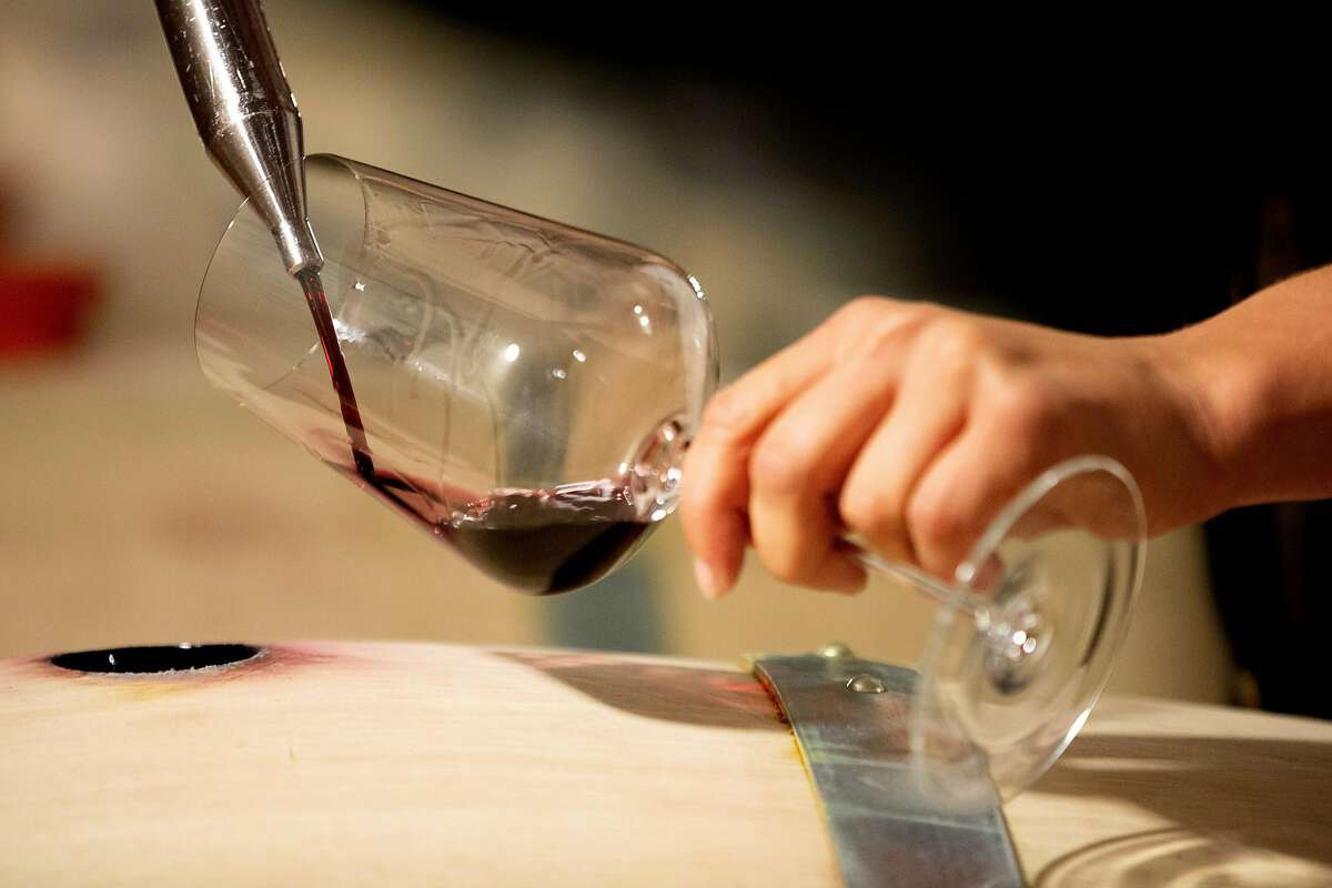 Winemaker Kathryn Carothers samples a wine from barrel at Bryant Estate.