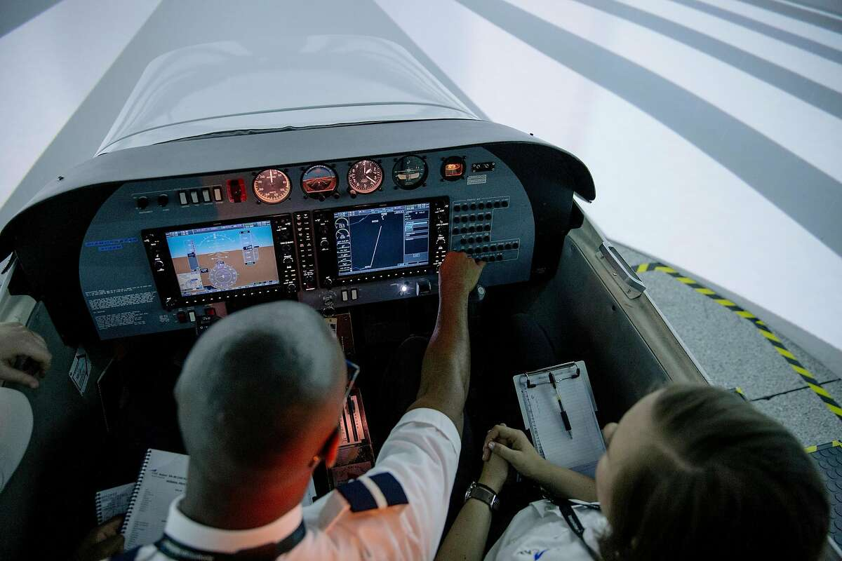 """**EMBARGO: No electronic distribution, Web posting or street sales before Monday 12:01 a.m. ET June 17, 2019. No exceptions for any reasons. EMBARGO set by source.** Olivia Mickevicius and Ahkeel Leach learn in a flight simulator at the American Airlines Cadet Academy in Mesa, Ariz., where they are training to become pilots, May 30, 2019. It's a conundrum bordering on a crisis for the global airline industry: More people are flying to more places, but the number of pilots is not keeping up. """"It's a great job, but not everybody knows there are affordable avenues or has guidance to get there,"""" Leach said. (Caitlin O'Hara/The New York Times)"""