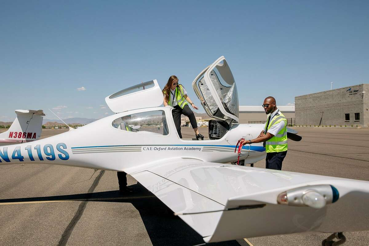 """**EMBARGO: No electronic distribution, Web posting or street sales before Monday 12:01 a.m. ET June 17, 2019. No exceptions for any reasons. EMBARGO set by source.** Olivia Mickevicius and Ahkeel Leach after a preflight equipment check at the American Airlines Cadet Academy in Mesa, Ariz., where they are training to become pilots, May 30, 2019. It's a conundrum bordering on a crisis for the global airline industry: More people are flying to more places, but the number of pilots is not keeping up. """"It's a great job, but not everybody knows there are affordable avenues or has guidance to get there,"""" Leach said. (Caitlin O'Hara/The New York Times)"""