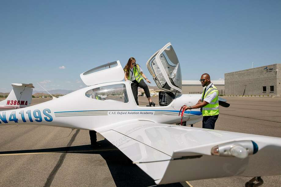 Olivia Mickevicius and Ahkeel Leach wrap up a preflight equipment check at the American Airlines Cadet Academy in Mesa, Ariz., where they are training to become pilots. Below: They use the flight simulator. Photo: Photos By Caitlin O'Hara / New York Times