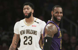 Los Angeles Lakers' LeBron James, right, smiles as he walks past New Orleans Pelicans' Anthony Davis during the first half of an NBA basketball game, Friday, Dec. 21, 2018, in Los Angeles.