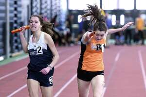 Taylor Mascetta (left) of Immaculate edges out Grace Michalowski of Ridgefield at the finish line in the 4x800 meter relay at the State Open track championship at the Floyd Little Athletic Center in New Haven on February 16.