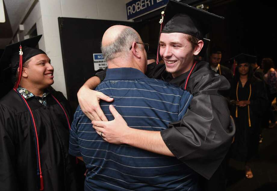 Retired plumbing teacher John Carew, back to camera, gets a hug from Joe Moncheski before Platt Technical High School graduation Monday. Photo: Arnold Gold / Hearst Connecticut Media / New Haven Register