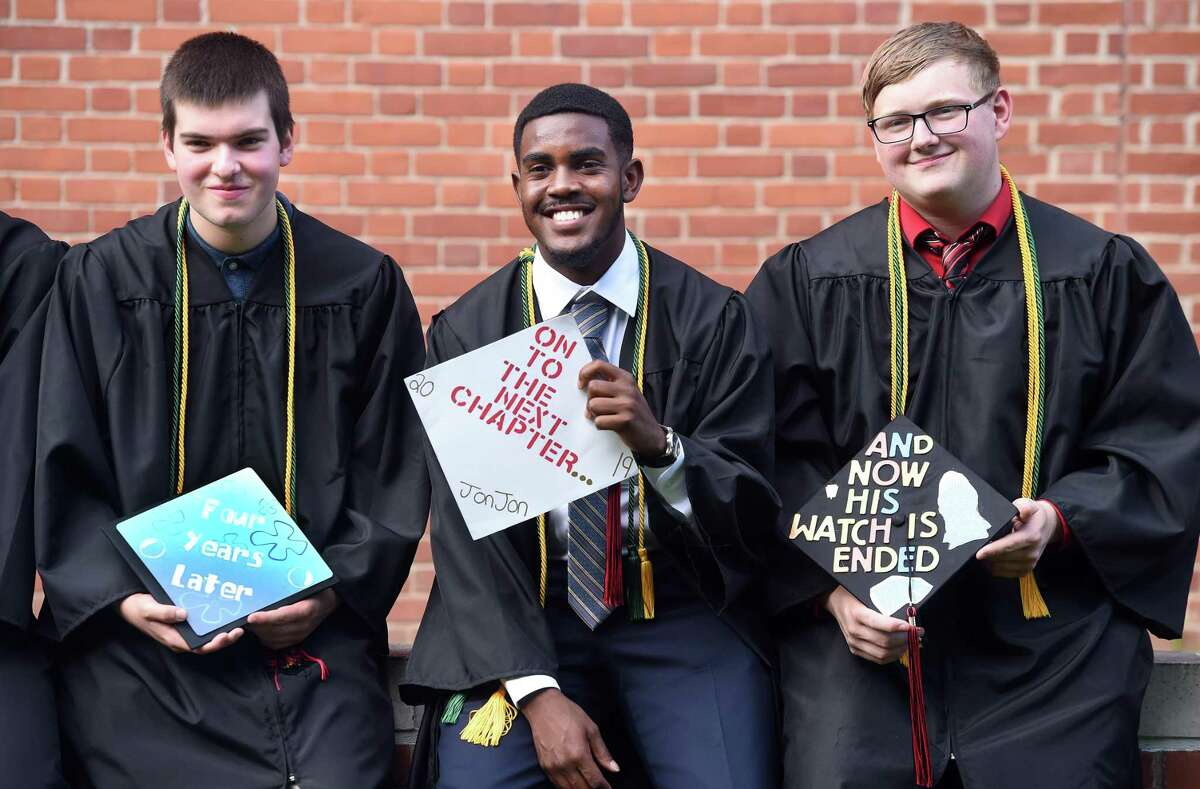 From left, Anthony DiMenna, Jonathan Smith and Michael Cropley show off their hats before the Platt Technical High School graduation begins at the John Lyman Center at Southern Connecticut State University in New Haven on June 17, 2019.