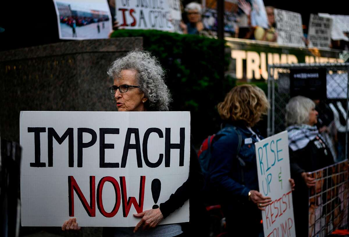 """A demonstrator with a sign reading """"Impeach now"""" takes part in Trumps Birthday Protest in front of the Trump International Tower, June 14, 2019 in New York City. - A group of activists protested against his immigration policy. (Photo by Johannes EISELE / AFP)JOHANNES EISELE/AFP/Getty Images"""