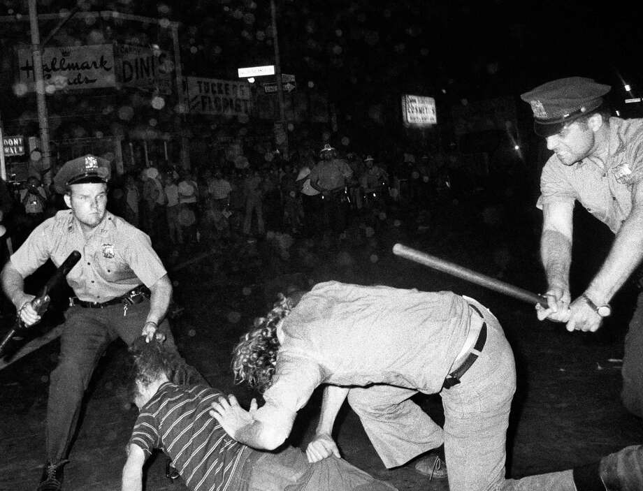 FILE - In this Aug. 31, 1970 file photo, an NYPD officer grabs a youth by the hair as another officer clubs a young man during a confrontation in Greenwich Village after a Gay Power march in New York. A year earlier, the June 1969 uprising by young gays, lesbians and transgender people in New York City, clashing with police near a bar called the Stonewall Inn, was a vital catalyst in expanding LGBT activism nationwide and abroad. (AP Photo/File) Photo: Anonymous / AP1970