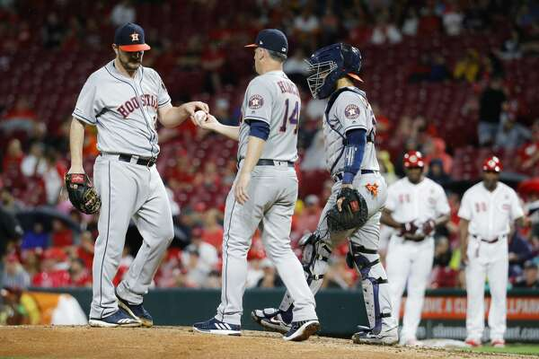 Houston Astros starting pitcher Wade Miley, left, is relieved by manager AJ Hinch (14) after walking Cincinnati Reds' Yasiel Puig in the fifth inning of a baseball game, Monday, June 17, 2019, in Cincinnati. (AP Photo/John Minchillo)