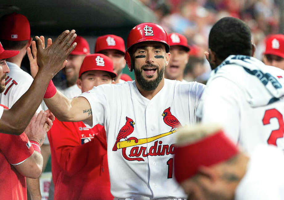 The Cardinals' Matt Carpenter is congratulated by teammates in the dugout after hitting a home run in the third inning of Monday night's game against the Miami Marlins at Busch Stadium.