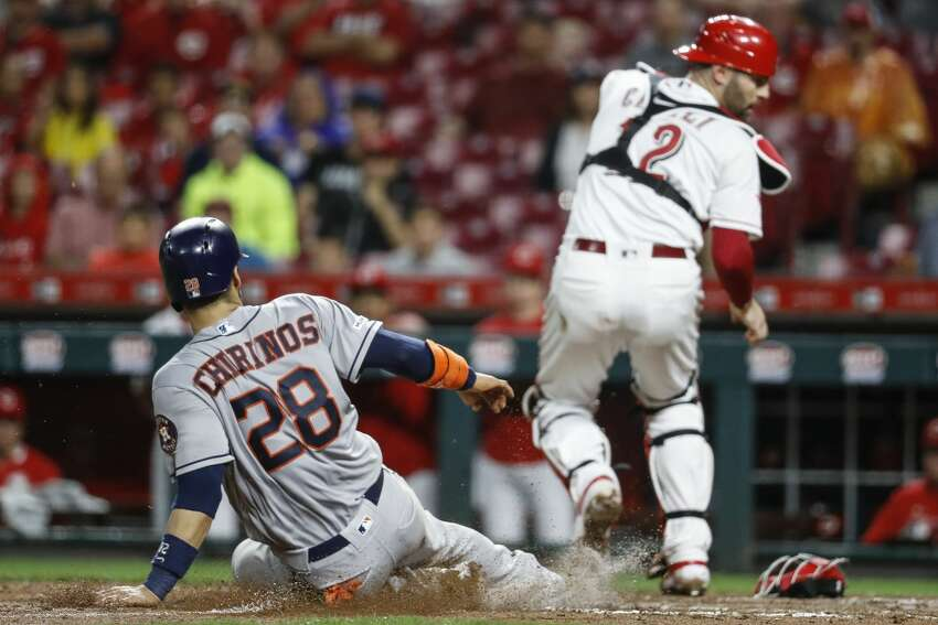 Houston Astros' Robinson Chirinos (28) scores on a throwing error by Cincinnati Reds second baseman Jose Peraza in the seventh inning of a baseball game, Monday, June 17, 2019, in Cincinnati. (AP Photo/John Minchillo)